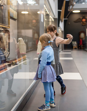 Girls of 7 and 5 years studying   exhibits in   museum.