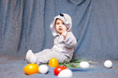 Baby   in rabbit costume and with Easter eggs.