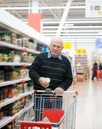 elderly man with   trolley in   supermarket between    racks.