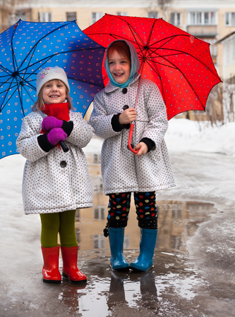 Portrait of little girls in boots and umbrellas in   spring.