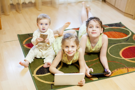 Three sisters of 9 months, 6  and 8 years playing in   gadgets on   carpet in   living room Reklamní fotografie