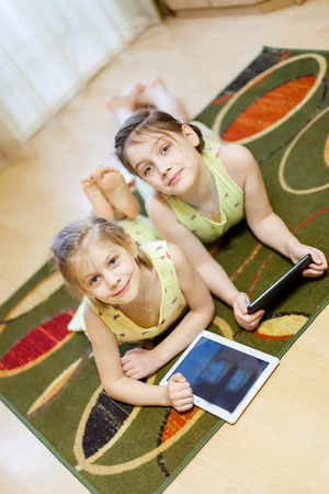 Two sisters of   6  and 8 years playing in   gadgets on   carpet in   living room