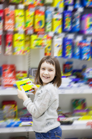 girl of 7 years old choosing stationery in   store.