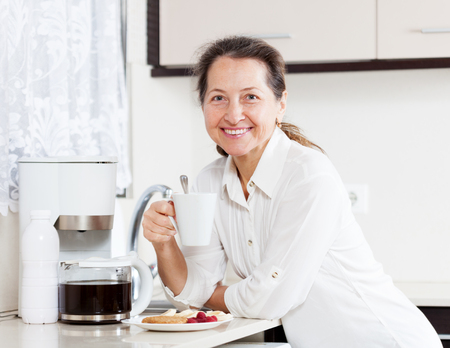Mature woman   eating coffee with cookies in   kitchen. Stock Photo