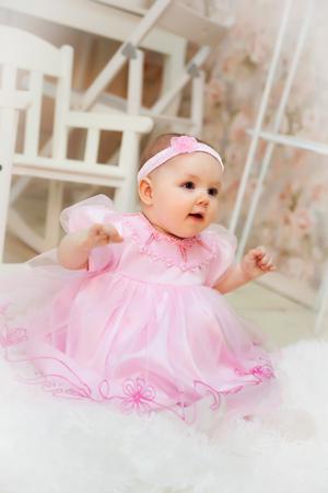 Portrait of   10-month-old girl in   festive dress in   studio.