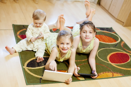 Three sisters of 9 months, 6  and 8 years playing in   gadgets on   carpet in   living room Stock Photo