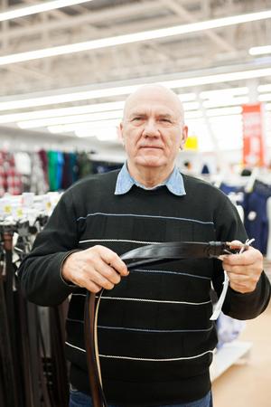 elderly man in   clothing store choosing purchases.