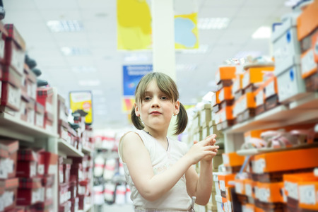 girl of seven years old choosing summer shoes in   store.