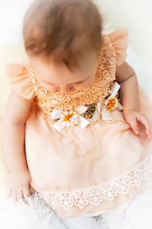 Portrait of   10-month-old girl in   festive dress in   studio