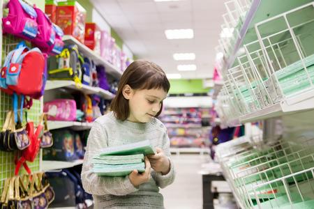schoolgirl choosing office supplies Stock Photo