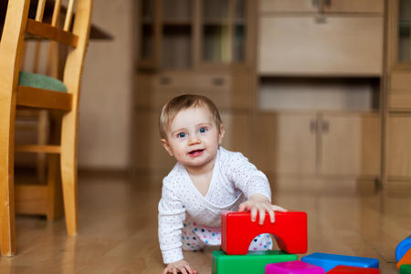 baby playing with plastic cubes on   floor in   room.