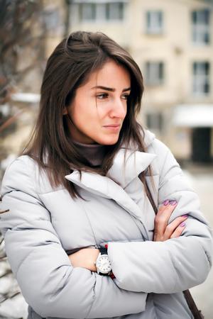 Portrait of   beautiful girl in   winter down jacket.