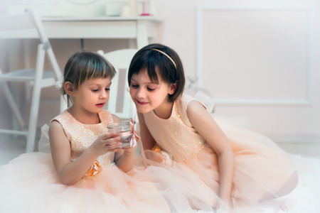Girls 5 and 7 years old  posing in  studio in beautiful festive dresses.