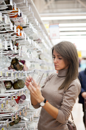 Girl in   supermarket near   showcase with dishes.
