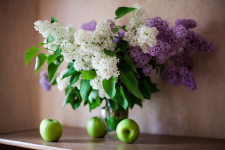 Still life with white and violet lilac on windowsill. Standard-Bild