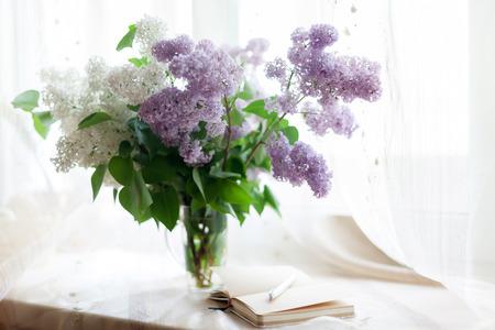 Schöner Fliederstrauß in Glasvase auf hellem Hintergrund.