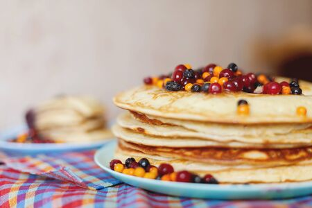 Still life with a stack of pancakes and berries