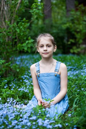 Portrait of eight-year-old  girl with forget-me-nots flowers
