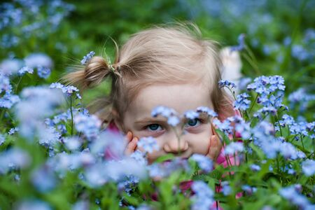 Portrait of  two year old girl with forget-me-nots flowers