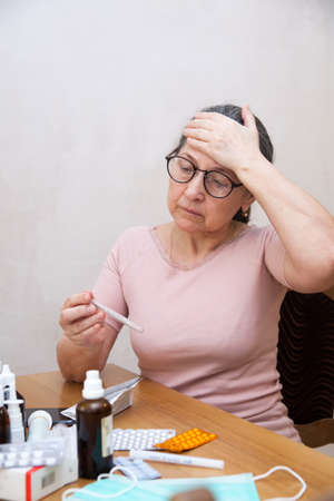 Elderly amazed woman reading annotation to medicines at table at home