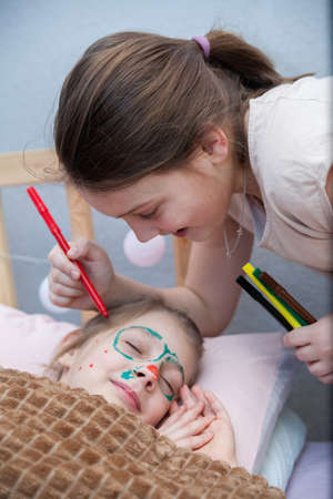 Girl drawing mustache on face of her sleeping sister. April fool's day Foto de archivo