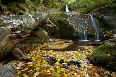 a small waterfall covered in autumn foliage Stock Photo