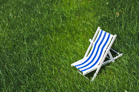 A decoration striped beach chair recliner for sunbathing and relaxing stands on a grass in a warm sunny day, side view