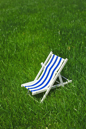 Classical decoration striped beach chair recliner for sunbathing and relaxing stands on a grass in a warm sunny day