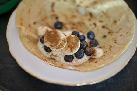 Breakfast of pancake, yogurt, whipped cream, sour cream, berries, blueberries, banana, cinnamon, in a white plate on a dark table, side view