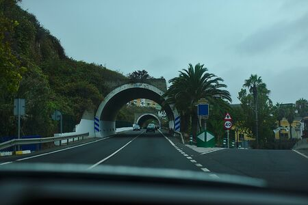 Road arch and crossroad, tunnel in the fog, in the mountains, cars.