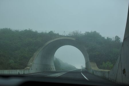 Road arch in the fog, a tunnel in the mountains.