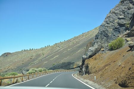 Asphalt road in a national park, in the mountains, sunny day, trip by car in nature, Canaries Island
