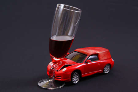 drunkenness: car entered in full glass on black background Stock Photo