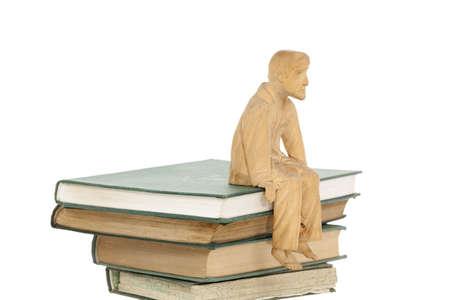 wooden men sculpture sit on heap of books Stock Photo - 11994750