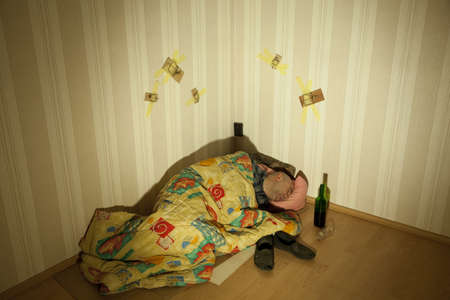 counterpane: lonely drunken men sleep in angle with bottle Stock Photo