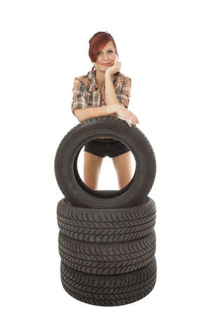Young girl stand near the car tyre on white background   photo