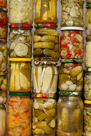marinated gherkins: vegetables different species marinated in jar as background