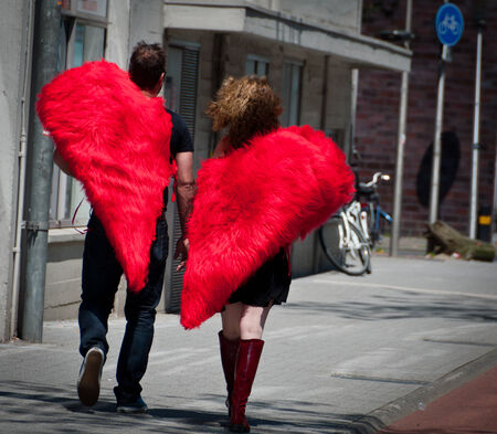 eindhoven: EINDHOVEN, NETHERLANDS - JUNE 8: An adult couple with half-heart shaped costumes walking in the street. Editorial