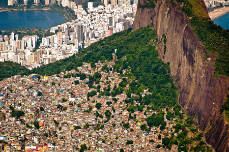 Aerial view of Favela da Rocinha, biggest slum in Brazil on the Mountain in Rio de Janeiro, and skyline of the city behind Stock Photo