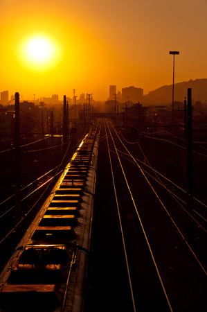Train Heading to the City in the Early Morning on Sunrise Stock Photo