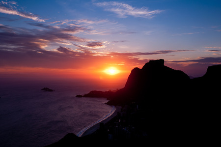topsail: Sunset in Sao Conrado Beach in Rio de Janeiro, Surrounded by Mountains, the Sun is Going Down Behind the Pedra da Gavea Rock