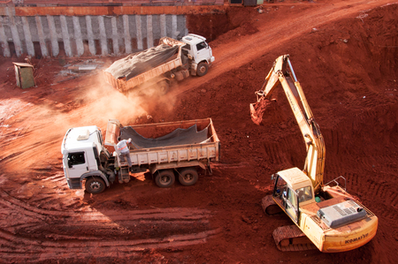 Brasilia, Brazil - June 6, 2015: Excavator loading dumper truck tipper in construction site of a new commercial building. Editorial