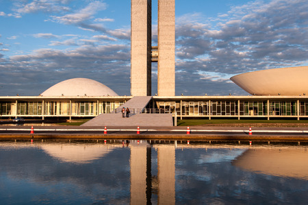 Brasilia, Brazil - June 3, 2015: Brazilian National Congress reflected on water by sunset. The building was designed by Oscar Niemeyer in the modern Brazilian style.