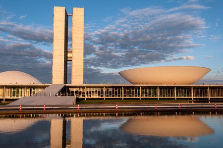 Brasilia, Brasilien - 3. Juni 2015: Brasilianischer Nationalkongress dachte über Wasser durch Sonnenuntergang nach. Das Gebäude wurde von Oscar Niemeyer im modernen brasilianischen Stil entworfen.