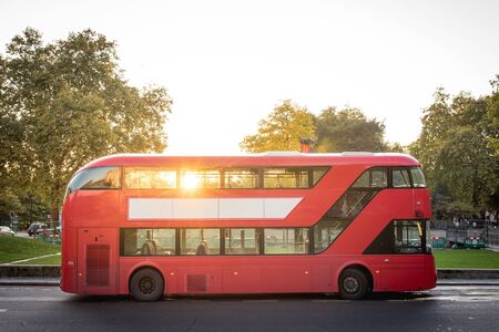 Red Double Decker Bus of London Parked Near the Park by Sunset Standard-Bild