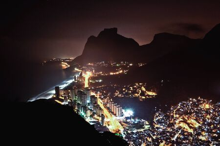 Night View of Sao Conrado District, a Bit of Rocinha Favela and Pedra da Gavea Mountain in Rio de Janeiro, Brazil