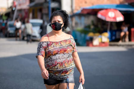 Rio de Janeiro, Brazil - July 3, 2020: People are wearing face masks during the Coronavirus pandemic in suburban area of the city. Woman crossing the street.