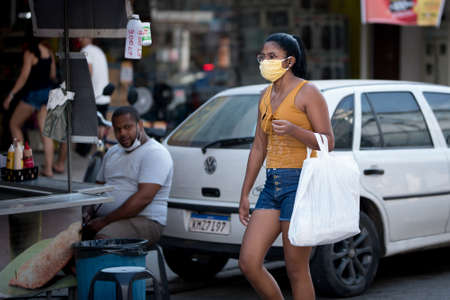 Rio de Janeiro, Brazil - July 3, 2020: People are wearing face masks during the Coronavirus pandemic in suburban area of the city. Woman with shopping bag passing while a man watches her.