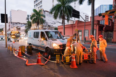 Rio de Janeiro, Brazil - July 2, 2020: Group of electrician workers are making repairs in the city street.