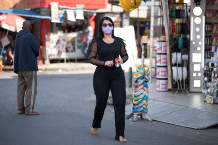 Rio de Janeiro, Brazil - July 3, 2020: People are wearing face masks during the Coronavirus pandemic in suburban area of the city. Woman dressed in black crossing the street.